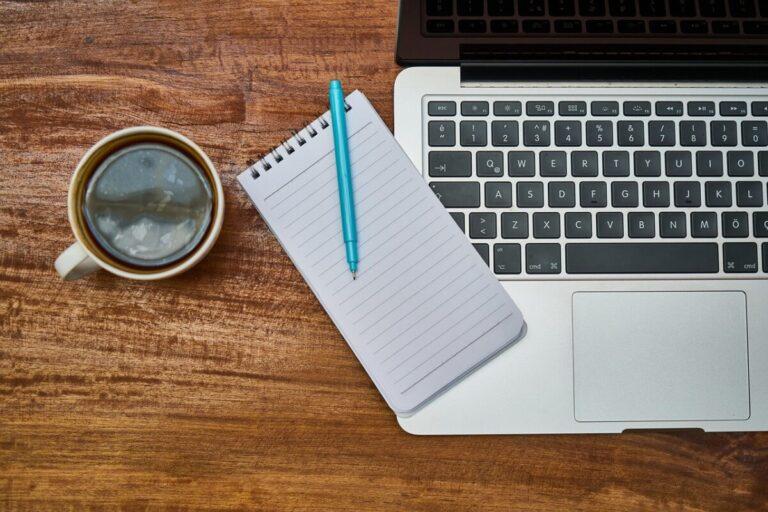 Notieboek met pen, kopje koffie en laptop