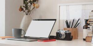 Laptop om je foto's uit te zoeken met ernaast een fotocamera op een bureau