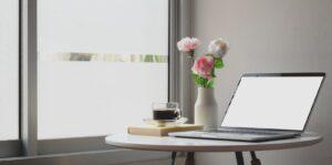 Laptop op ronde tafel met bosje bloemen