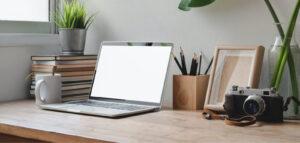 Laptop op bureau met ernaast een fotocamera.
